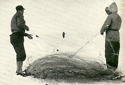 One man takes either side as they pull the fish net out from the frozen lake.
