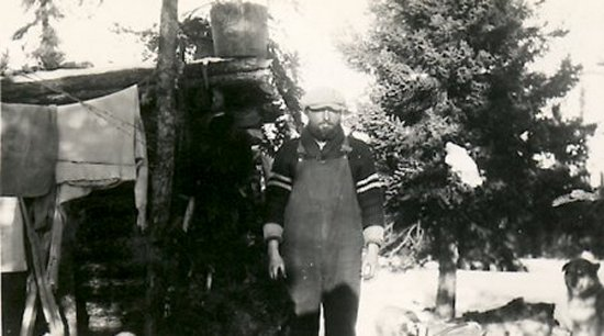Ed Theriau beside his trapping cabin