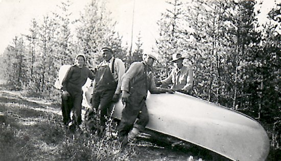 Ed theriau and Fred darbyshire portaging a canoe