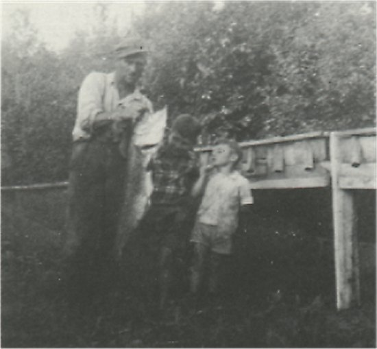 March, 1958. Robert Snell holding fish. Sons Bob and Ken, standing by. Fish measured 42 inches long.